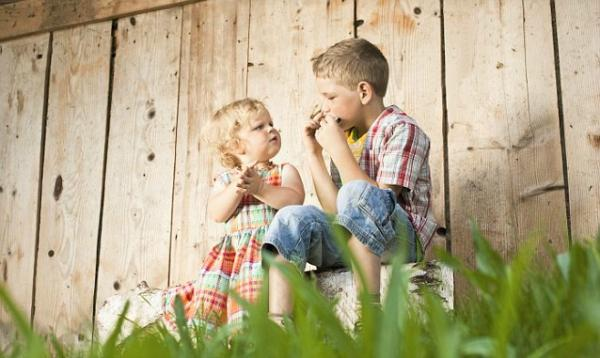 Boy And Girl Sitting Outside In Garden600x385